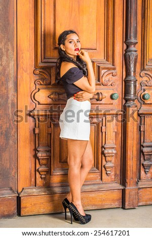 Dressing in black, short sleeve top, white short fit skirt, high heals, a young student standing by library door, a hand touching her chin. Concept of teenagers growing, questioning life, self esteem. - stock photo