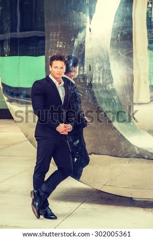 Dressing in black suit, leather shoes, a young, strong, sexy businessman casually standing by metal mirror wall, crossing legs, holding hands, looking at you, thinking. Instagram filtered effect. - stock photo