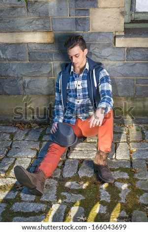 Dressing in blue, white pattern shirt, a hoody vest,  red jeans and brown leather boot shoes, holding a woolen Fedora hat on his knee, a young guy is sitting on the ground into deeply thinking.  - stock photo
