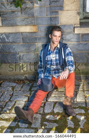 Dressing in blue, white pattern shirt, a hoody vest,  red jeans and brown leather boot shoes, holding a woolen Fedora hat on his knee, a young guy is sitting on the ground into deeply thinking.