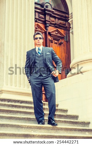 Dressing in dark blue three pieces suit, necktie, vest, leather shoes, wearing sunglasses, a handsome, sexy, middle age businessman walking down stairs from office building. Instagram filtered look. - stock photo