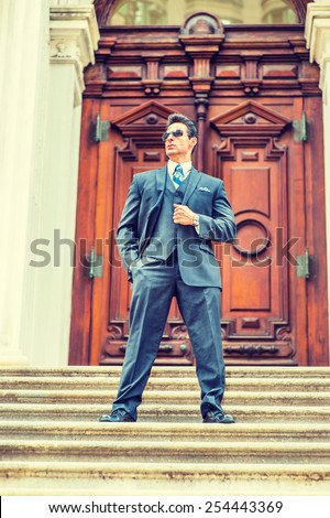 Dressing in dark blue three pieces suit, necktie, vest, leather shoes, wearing sunglasses, a handsome, sexy, middle age businessman standing on stairs in the front of office. Instagram filtered look. - stock photo