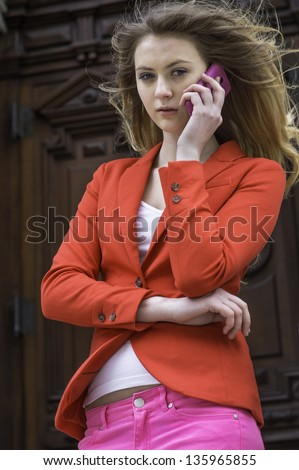 Dressing in red blazer and pink pants, a young teenager girl is talking on the phone in a windy day. - stock photo