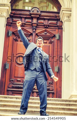 Dressing in three pieces suit, necktie, a handsome, sexy, middle age businessman standing on stairs in the front of office, raising his arm, yelling, celebrating his victory.  Instagram filtered look. - stock photo