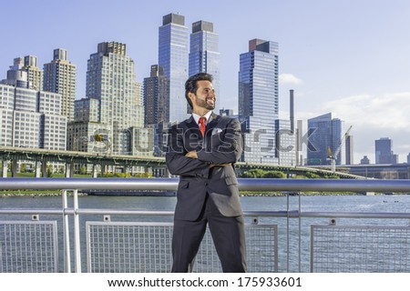 Dressing is a black suit, a red tie, crossing arms, a sexy, middle age businessman with mustache and beard is standing in the front of a business district, confidently looking forward. /Businessman - stock photo
