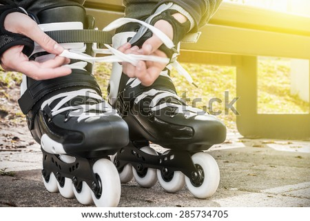 dressing roller skates for skating. focus in the middle of the frame on roller skates - stock photo