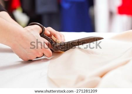 Dressmaker cutting fabric with big old steel scissors - stock photo