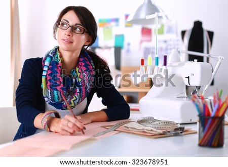 Dressmaker designing clothes pattern on paper