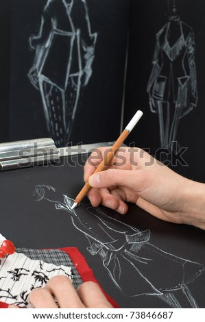 Dressmaker is drawing a fashion sketch - stock photo