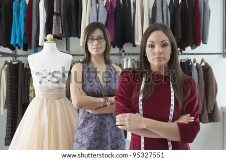 Dressmakers standing beside mannequin in clothing store - stock photo