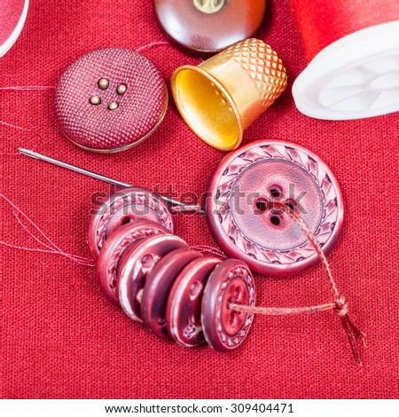 dressmaking still life - top view of bobbins with sewing thread, buttons, thimble, needle on red fabric - stock photo