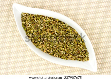 Dried and chopped oregano in stylish glass container - stock photo