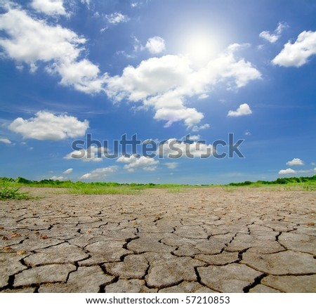 Dried and cracked soil in blue sky - stock photo