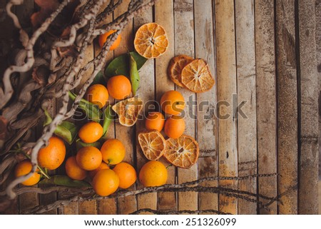 dried and fresh mandarin (tangerine)   on brown wood board  background in rustic style. - stock photo