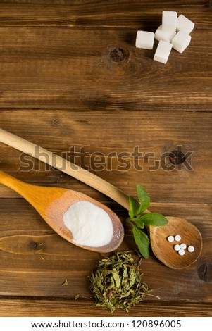 Dried and processed natural sweetener stevia together with real sugar lumps on a wooden table - stock photo