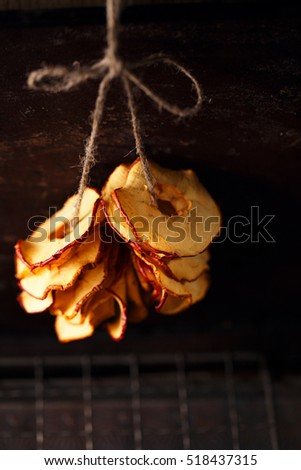 Dried apple slices hanging on string with dark metal backdrop and copy space