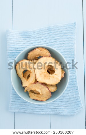 Dried apple slices in a blue bowl - stock photo