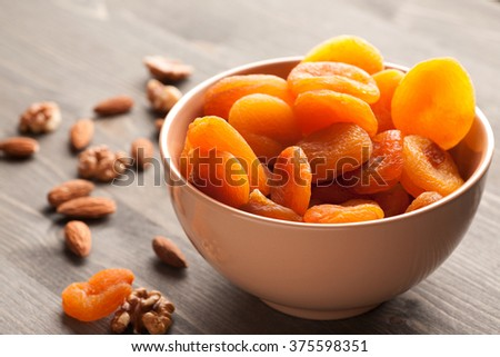 Dried apricots  and nuts on old wooden table close-up shot, selective focus - stock photo
