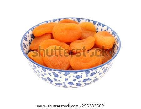 Dried apricots in a blue and white porcelain bowl with a floral design, isolated on a white background - stock photo