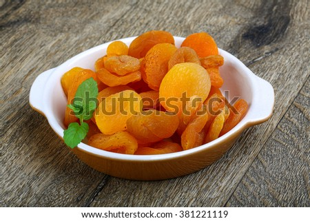 Dried apricots in the bowl on the wood background