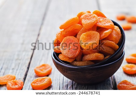 dried apricots on a dark wood background. tinting. selective focus - stock photo