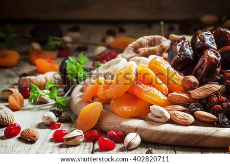 Dried apricots, set of nuts and dried fruits, vintage wooden background, selective focus - stock photo
