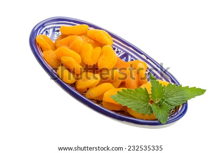 Dried apricots with melissa leaves isolated on white background