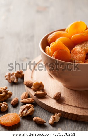 Dried apricots with nuts in a bowl on wooden table, selective focus, vertical - stock photo