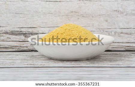 Dried bakers yeast in white bowl over wooden background - stock photo