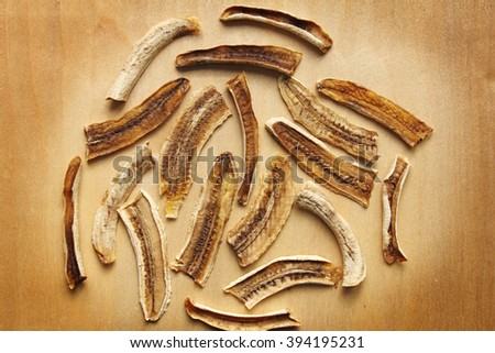 dried banana (raw food sweet banana chips) on the wooden table, vignette