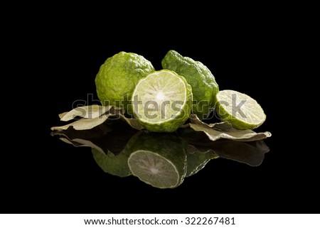 Dried bergamot leaves and fresh fruits isolated on black background. Culinary cooking, tropical fruit bergamot orange. - stock photo
