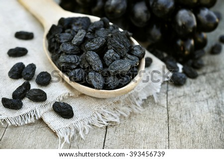 Dried black raisins in wooden spoon with fresh ripe grapes - stock photo