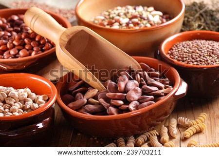 dried broad beans in the bowl with other vegetables around - stock photo