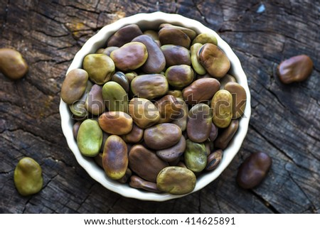 Dried broad beans on old wooden table - stock photo