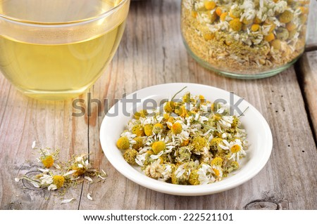 Dried camomile flowers on saucer. Chamomile tea in a transparent cup and dried camomile flowers on wooden table. Herbal tea for baby's stomach. - stock photo