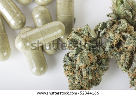 Dried cannabis bud and green pills - stock photo