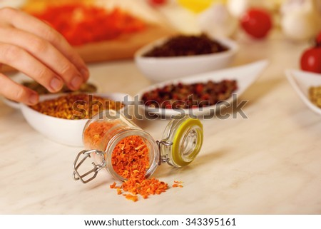 Dried carrots and variety of spices on the kitchen table - stock photo