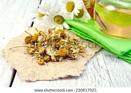 Dried chamomile flowers on paper, tea in glass teapot on a napkin, fresh daisy flowers on a background of pale wooden plank - stock photo