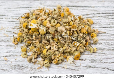 Dried chamomile herbal tea over wooden background - stock photo