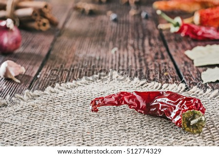 Dried chili pepper on sackcloth with various dried spices on the background. Selective focus