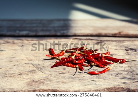Dried chili peppers on a wooden background. Spicy food ingredient.  - stock photo