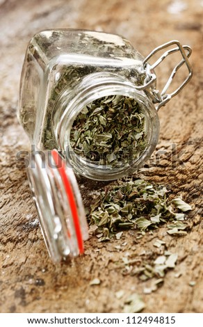 Dried cooking herbs in an opened glass bottle lying on its side spilling out onto an old rustic wooden tabletop - stock photo