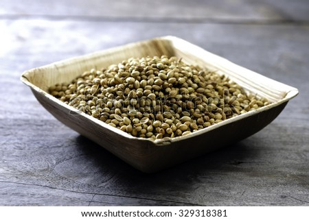 Dried coriander seeds in a wooden plate on a wooden table  - stock photo