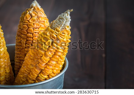 Dried Corn Stalk in bucket on wood table - stock photo