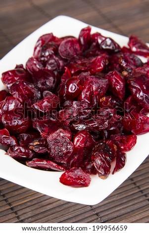 Dried cranberries in a bowl on a brown background - stock photo