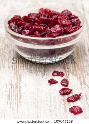 Dried cranberries in glass bowl on wooden table - stock photo