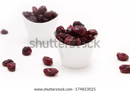 Dried cranberries in white bowls on white background - stock photo