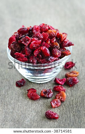 Dried cranberries spilling out of glass bowl - stock photo