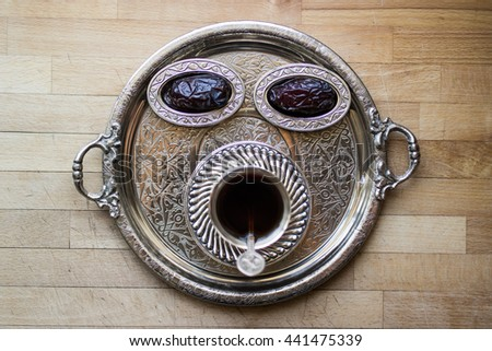 Dried date fruit with tea in a silver tray top view
