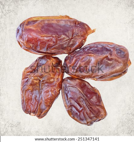 Dried date fruits. Paper texture. Aged textured photo in retro style - stock photo